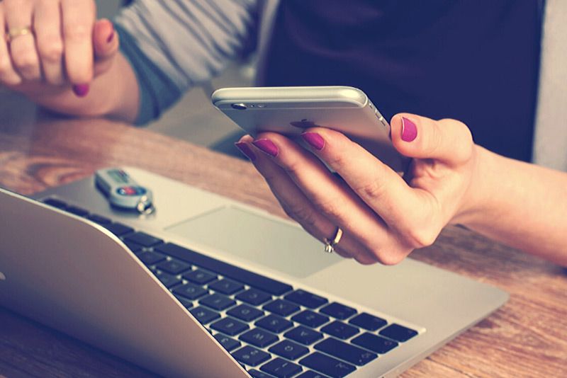 woman with mobile phone in hand at laptop