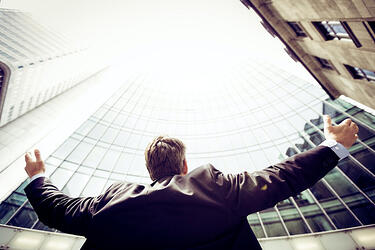 man in suit with arms wide looking up amont tall buildings
