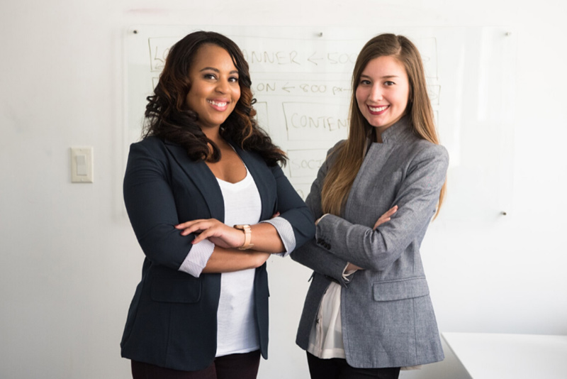 two women standing arms folded smiling in front of whiteboard